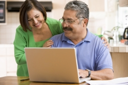 A couple happily planning their estate at home on a laptop